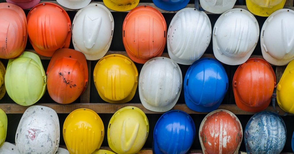 different colored hard hats lined on a wall